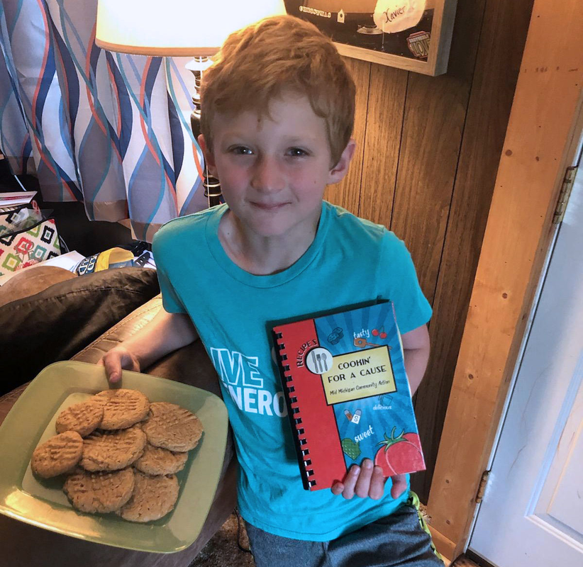 Community Spotlight: Cameron, one of our volunteers, with his cookbook from the volunteer appreciation picnic